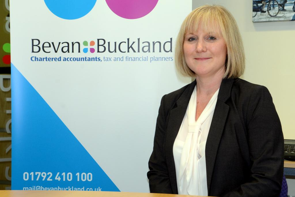 Sara Dennis, Director of Bevan Buckland with branding in background