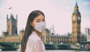 Female with facemask on outside the houses of parliament.